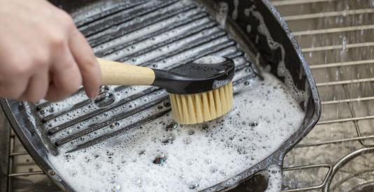 A person uses the scrub brush to wash a soapy Lodge Cast Iron Grill Pan in the sink.